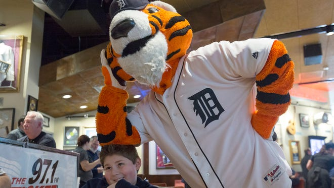 Paws, the Detroit Tigers' mascot, rests his arm on top of Michael Manjano, 9, of Monroe, while waiting for his food during the Tigers' winter caravan on Thursday, Jan. 19, 2017 at Hard Rock Cafe in downtown Detroit.