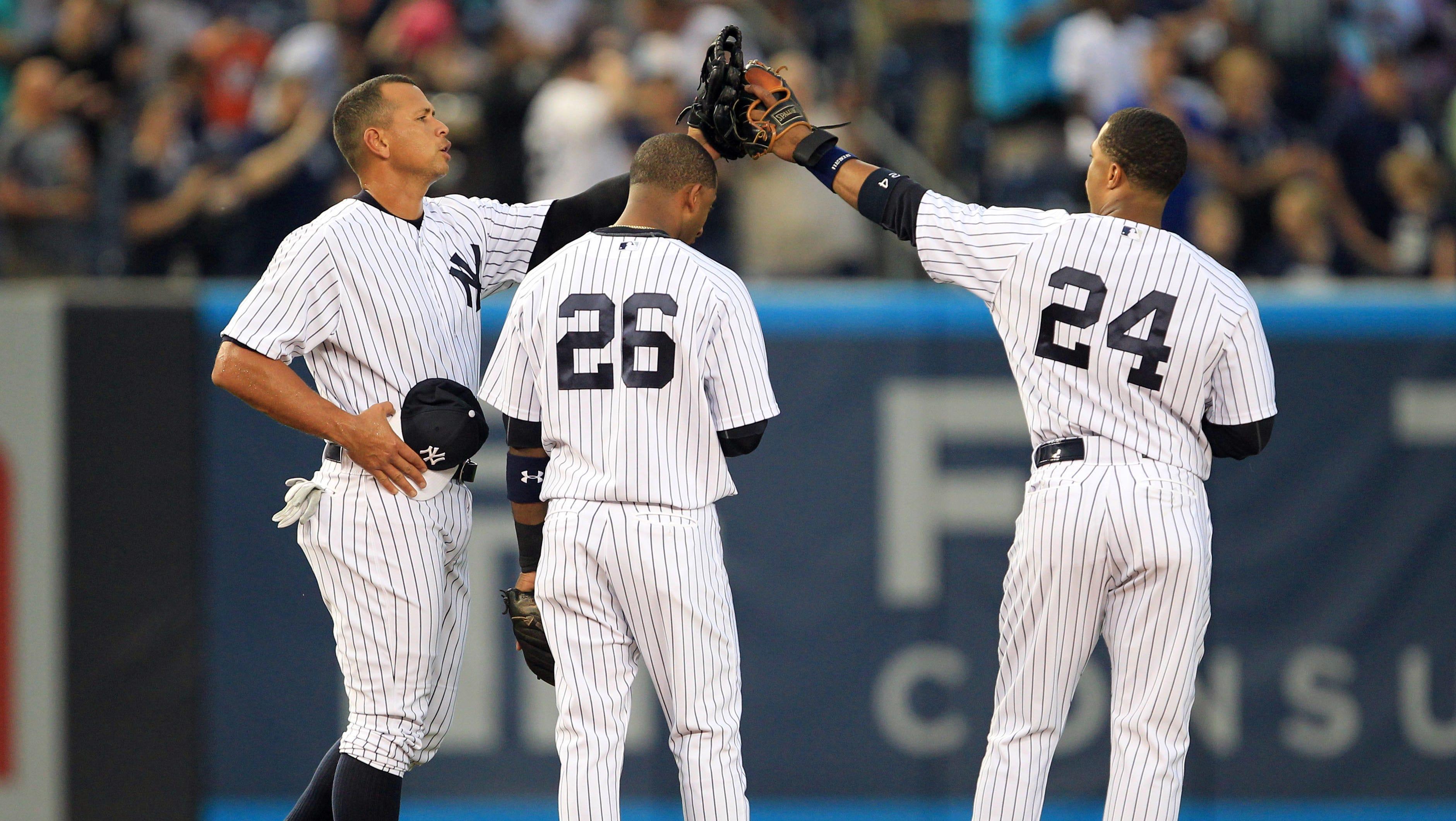 Alex Rodriguez, Eduardo Nunez and Robinson Cano high five after the National Anthem.