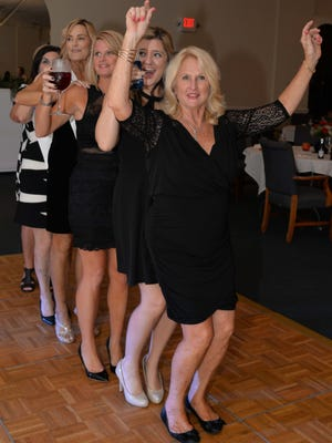 Gail Flesche leads the conga line at the Little Black Dress cocktail party to benefit the VIM/HANDS Clinic of St. Lucie County.