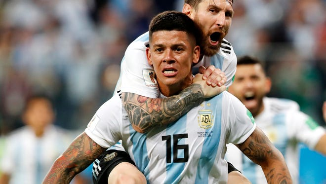 Marcos Rojo of Argentina celebrates with teammate Lionel Messi.