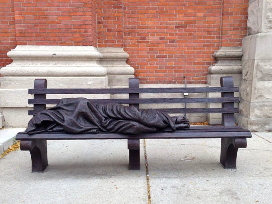 """A """"Homeless Jesus"""" statue is in front of Saints Peter"""