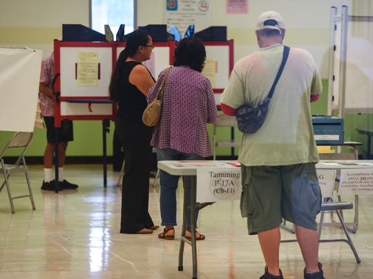 Througn a window, voters could be seen casting their General Election ballot, at the polling site at John F. Kennedy High School in Tamuning on Tuesday, Nov. 8, 2016.