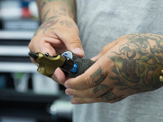 Alex Trujillo preps his tattoo gun before a client settles into get a tattoo. Trujillo's focus on sanitation has led the state licensing board to use his shop as an example of how work should be done. Aug. 28, 2017.