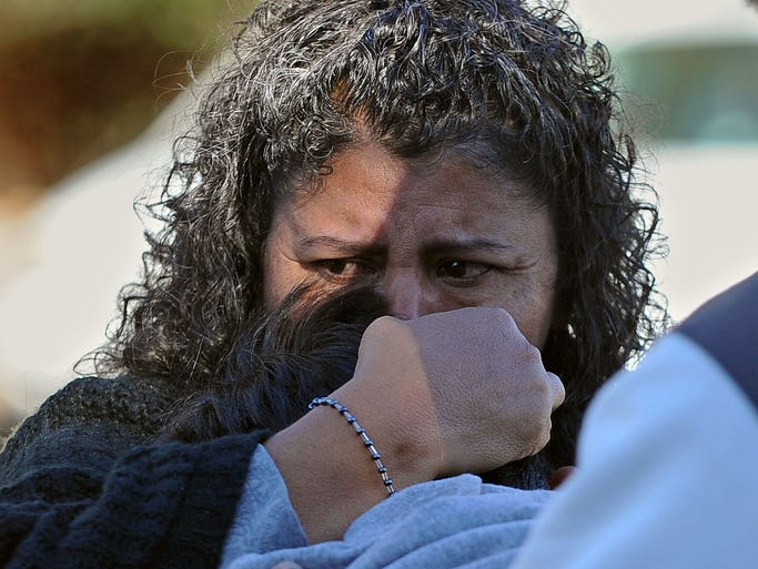 A woman holds her son after picking him up at Sparks High School on Monday.