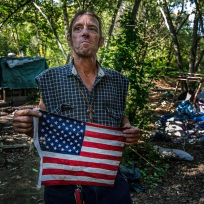 Chris Scott holds the American flag that hung over