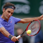 Roger Federer returns the ball to Gael Monfils during their fourth-round French Open match Sunday in Paris.