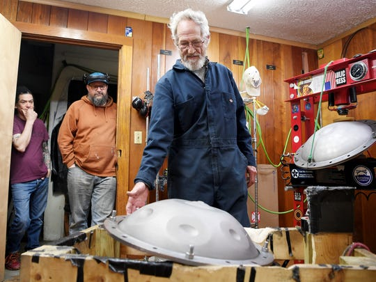 Steve Garner shows the note hollows he punches into the Saraz handpans with a hydraulic press as Chris Genereaux, left, and Chet Plant look on April 17, 2018 in Black Mountain.