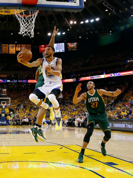 Golden State Warriors' Stephen Curry drives past Utah Jazz's Rudy Gobert (27) and another defender during the first half in Game 1 of an NBA basketball second-round playoff series, Tuesday, May 2, 2017, in Oakland, Calif. (AP Photo/Marcio Jose Sanchez)