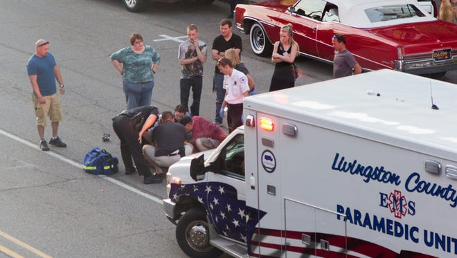 Livingston County paramedics tend to a 53-year-old Howell man, who was injured Saturday when a Dodge Caravan rear-ended his motorcycle on Grand River Avenue in downtown Howell.