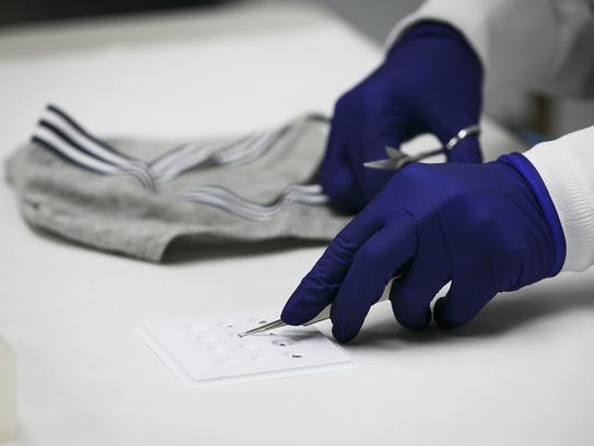Forensic scientist Jennifer Buttler cuts small pieces