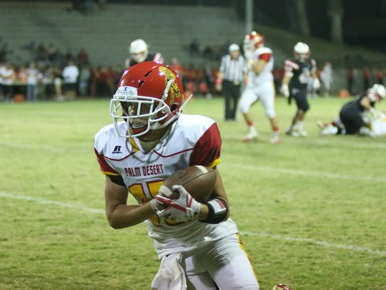Palm Desert's Simon Gaete gains yards after a catch