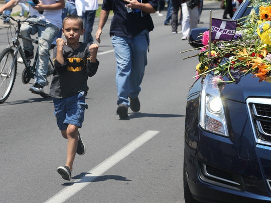 A young man man runs beside the hearse carrying the