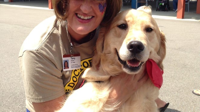 Terri Seraceno of Farmington Hills, founder of Dr. Paws Pet Assisted Therapy, with Maria, a 3-year-old golden retriever therapy dog at a July Make-A-Wish event in Brooklyn, Mich.