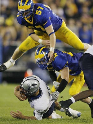 University of New Hampshire receiver Keith LeVan (bottom) is tackled by Delaware linebacker Erik Johnson (57) and Garrett Schultz after picking up a first down in the fourth quarter of the Blue Hens' 52-49 loss at Delaware Stadium on Sept. 30, 2006.