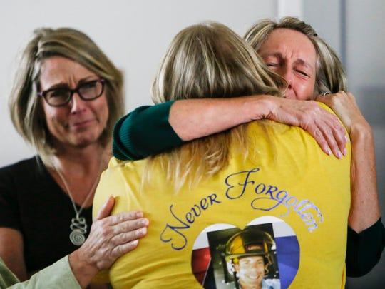 """Dennis Rodeman's sister, Kelly Flory of Vermontville, middle, hugs Karen Taylor, right, mother of Grant Taylor, who was sentenced Sept. 7, 2017 to 30 to 40 years in prison for Rodeman's murder.  Also pictured is Taylor's aunt Deb Cook of Lansing, who sat with her sister throughout the hearings for the past two years.  """"We needed that hug,"""" Cook said.   [Matthew Dae Smith/Lansing State Journal]"""