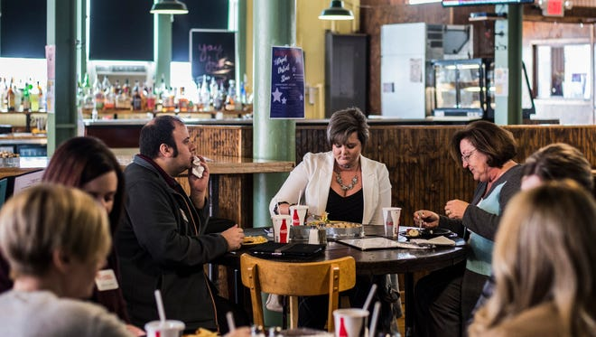 Locals eat lunch with a friend during the Depot District Italian Market's preview day for Wayne County Area Chamber of Commerce members on Monday, March 12, 2018.