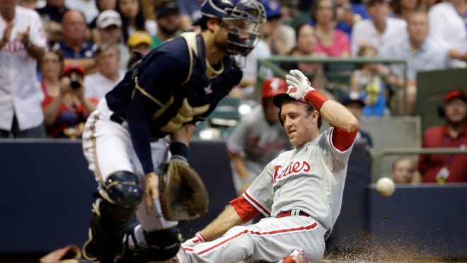 The Phillies' Chase Utley slides safely home past Brewers catcher Jonathan Lucroy during the third inning Monday in Milwaukee.