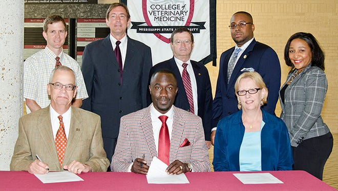 Seated in photo from left: MSU-CVM Provost Jerry Gilbert, Mayor Tony T. Yarber, and Zoo Director Beth Poff signing the memorandum of understanding.