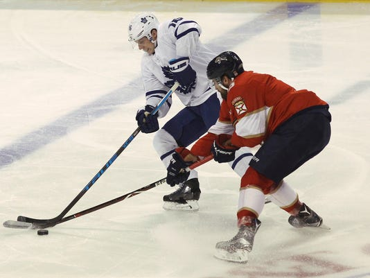 Toronto Maple Leafs' Mitchell Marner, left, and Florida Panthers' Aaron Ekblad, right, battle for the puck during the first period of an NHL hockey game, Wednesday, Nov. 22, 2017, in Sunrise, Fla. (AP Photo/Luis M. Alvarez)