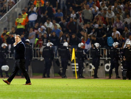 Serbia's Coach Dick Advocaat, left, leaves from pitch during the Euro 2016 Group I qualifying match between Serbia and Albania, at the Partizan stadium in Belgrade, Serbia, Tuesday, Oct. 14, 2014. The European Championship qualifier between Serbia and Albania was suspended on Tuesday after pitch skirmishes involving players and fans over an Albanian flag that was flown above the stadium by a drone. (AP Photo/Darko Vojinovic)