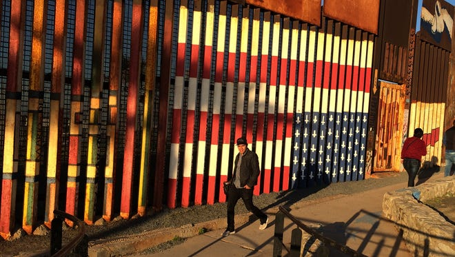 """People pass graffiti along the border structure in Tijuana, Mexico, Wednesday, Jan. 25, 2017. President Donald Trump moved aggressively to tighten the nation's immigration controls Wednesday, signing executive actions to jumpstart construction of his promised U.S.-Mexico border wall and cut federal grants for immigrant-protecting """"sanctuary cities."""""""