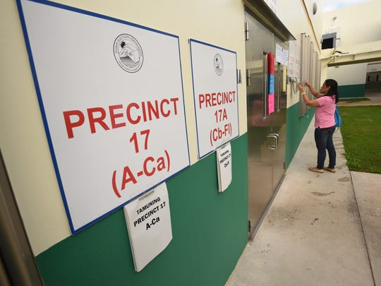 A woman checks for her name on a list of registered voters at the polling site in John F. Kennedy High School in Tamuning during the General Election on Tuesday, Nov. 8, 2016.