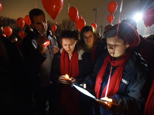 """Members of Andrew's family, Jackie (C), Emily (L) read a letter of remembrance to him as his mother Kathy (behind Jackie) and his father Frank (not shown but standing behind Emily) during a  """"Community Remembrance Vigil"""" for Saddle Brook High School student Andrew Gutierrez at Veteran's Field in Saddle Brook on 02/19/18.  Andrew Gutierrez, a SBHS 10th grader, suddenly and unexpectedly passed away at home on Friday, February 16th."""