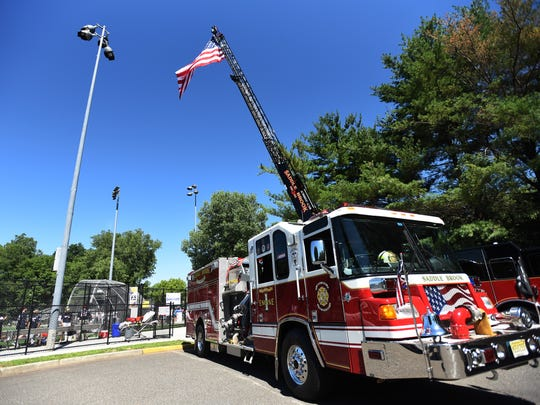 An American flag, hanging from the top of a firetruck's ladder, waves in the gentle breeze at Sunday's softball game.