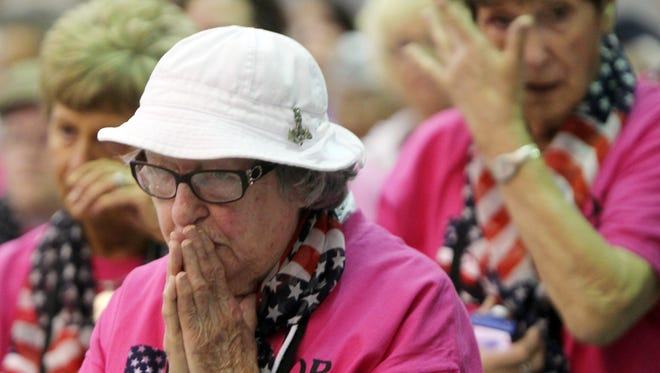 World War II Navy veteran Dorothy Kennedy reacts as women veterans behind her wipe away tears as the American flag is folded during a send-off ceremony for Tuesday's all-women Honor Flight Tri-State from Cincinnati/Northern Kentucky International Airport to Washington, D.C. They were among 72 women who made the flight to visit war memorials, including one for women veterans.