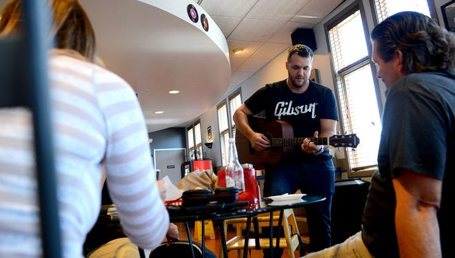 "New owner David Lopez jams on his guitar surrounded by family and friends as Coffee Jam celebrates its ""grand re-opening"" after finishing renovations under new ownership Monday, August 1, 2016. Lopez wants to play off the name ""jam"" and have music throughout the shop. There's a mini-stage for impromptu music performances and many of the drinks are musically themed."