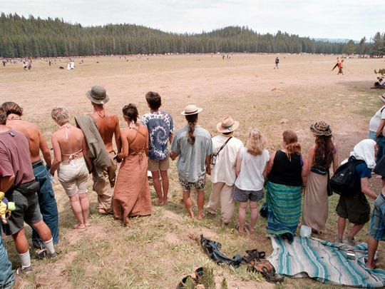 Participants at an earlier Rainboy Family Gathering in Idaho hold hands an form a circle. Up to 20,000 members of the Rainbow Family will be arriving in the Green Mountain National Forest near Mount Tabor this week for the annual Rainbow Gathering.