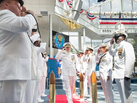 Retiring Rear Adm. Michael White, center, is saluted during the Piping the Side custom at the Naval Education and Training Command change of command ceremony at the National Naval Aviation Museum in Pensacola on Thursday, July 20, 2017.
