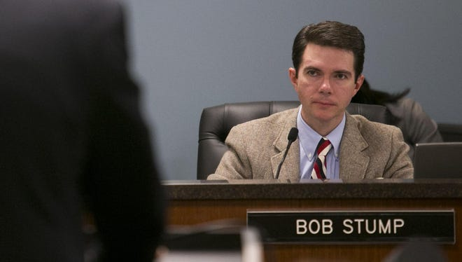 Bob Stump, then-chairman of the Arizona Corporation Commission, listens as Jeff Guldner, APS senior vice president, speaks at a hearing on rooftop solar rates in November 2013.