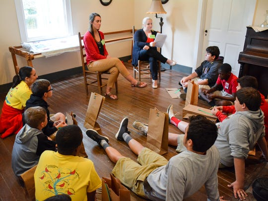 Judice Middle School eighth-grade students listen to a lesson on Acadian and Creole history during the Vermilionville Education Enrichment Partnership on Monday.