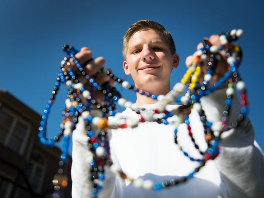 Sam Brown, 17, holds a string of beads he received