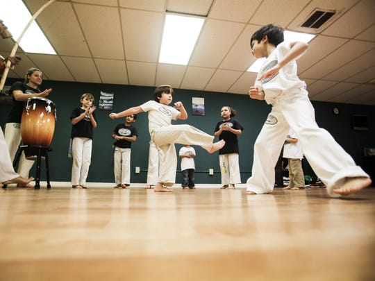 Students begin class with a circle warm-up where they rotate in and out performing various Brazilian capoeira moves on Wednesday, Dec. 14, 2016.