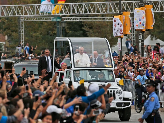 Pope Francis waves to the crowd from the popemobile during a parade on the Ben Franklin Parkway, in Philadelphia.