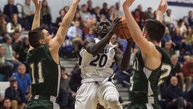 Mount Mansfield's Deng Adiang, center, tries to split the St. Johnsbury defense during Friday night's boys basketball game in Jericho. MMU won 58-56 on a buzzer-beating 3-pointer in overtime.