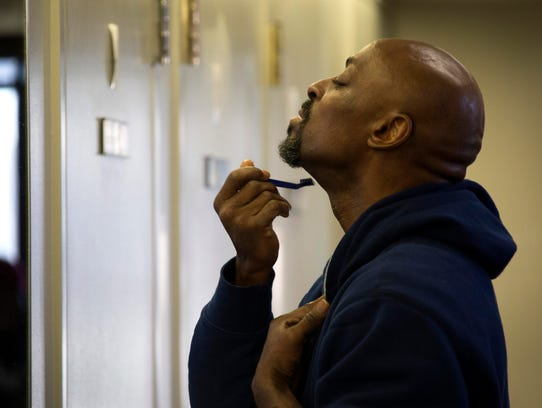 Ron Jackson, 53, takes a moment to shave inside the