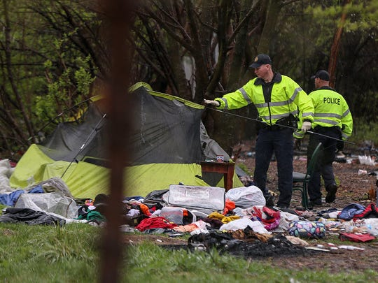 CSX Transportation Railroad Police begin their walk-through of the Jungle homeless camp, Indianapolis, Friday, March 31, 2017. Campsites were mostly vacant by Friday morning, though about a dozen residents remained. At 9:15 a.m., the CSX Transportation Railroad Police began taking down tents that were not yet collapsed.