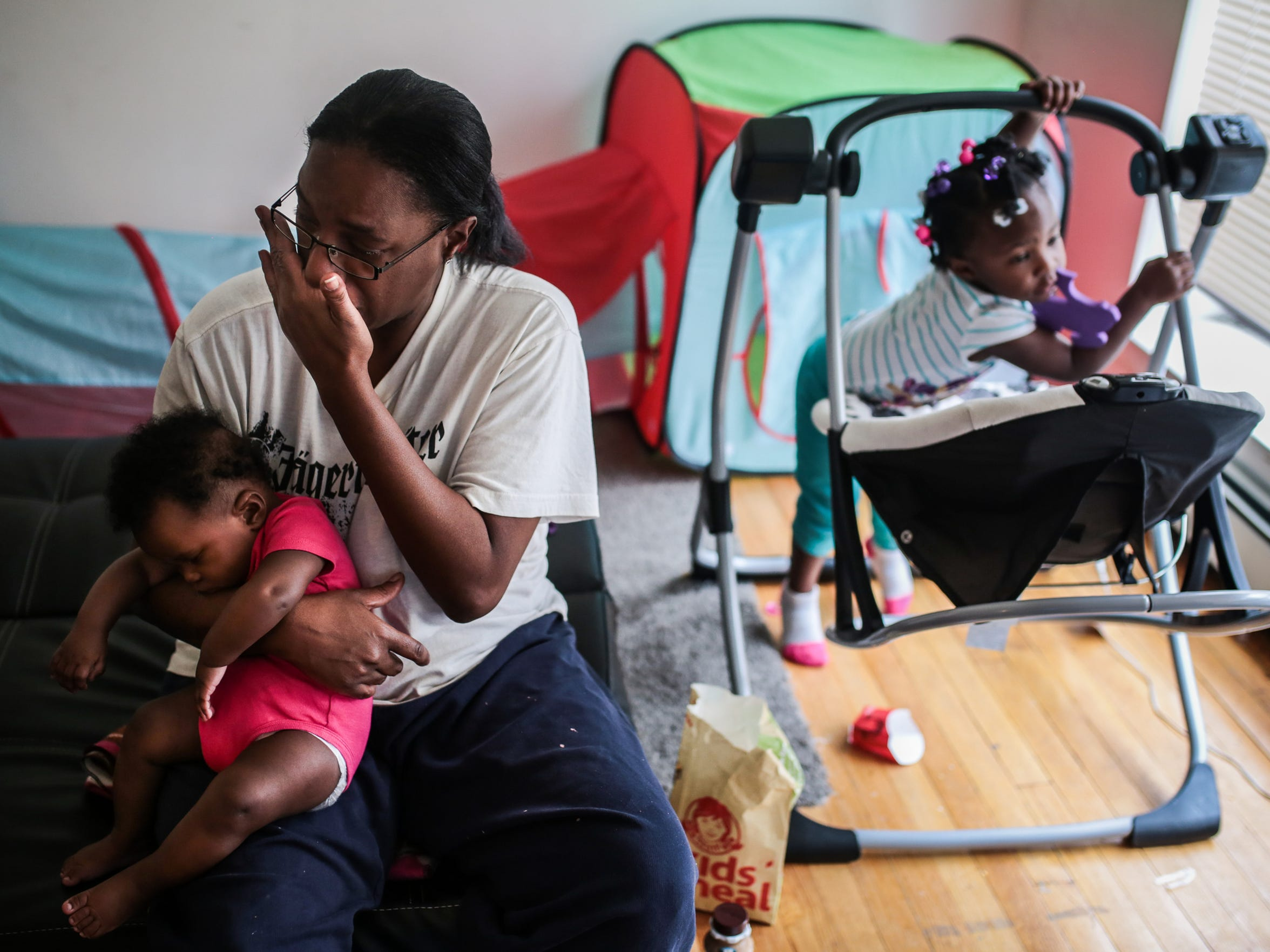 "Felicia Darnell, 40, of Detroit, cries as she speaks about her life while holding 4-month-old daughter Geneva Darnell inside their East McNichols Road apartment on Feb. 28, 2017. With no job, Felicia spends nearly all her time in this apartment with her two kids. ""Maybe once a week I scream about it,"" she said, ""but I have to realize I'm the only one who's here to take care of them."""