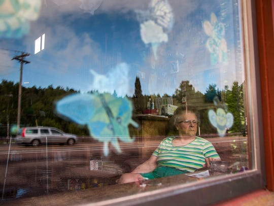 Arbutus Peterson, 84, of Phoenix, Mich., watches traffic passing by the Phoenix Store, an old-fashioned general store built in 1873. It's the town's only functioning business. She's the store's owner and its sole employee, working 11 hours a day, seven days a week.