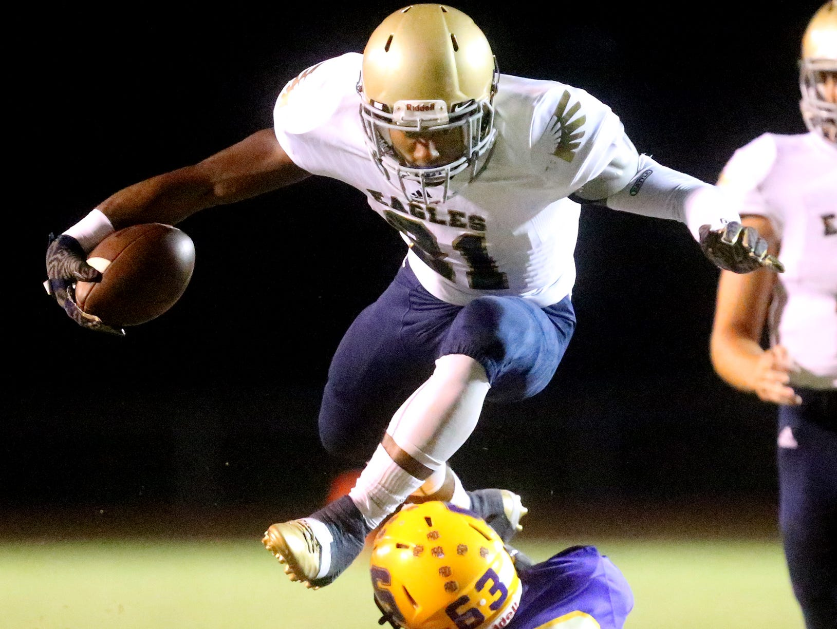 Independence's Troy Henderson (21) hurdles over players as he runs the ball during the game against Smyrna.