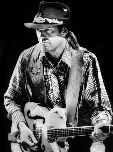 Neil Young, with his backing band, the International Harvesters, performs at the Grand Ole Opry House on Sept. 18, 1984.