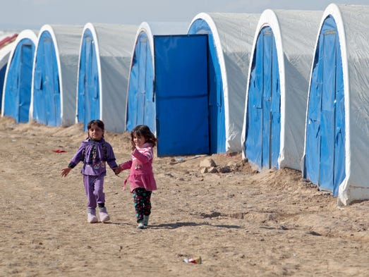 Displaced Iraqi girls walk holding hands at the Al-Agha