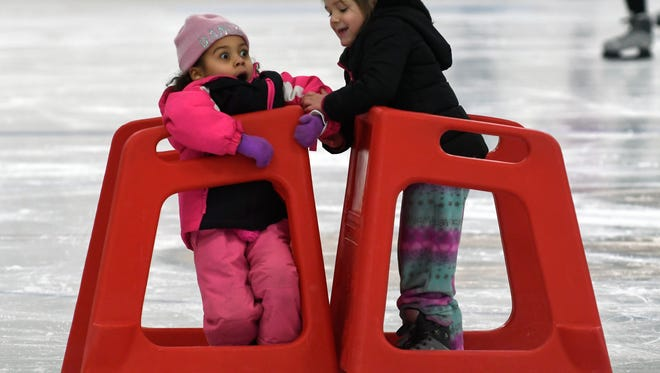 Young skaters help each other as they learn to skate during open skate at The Rink Sunday afternoon.
