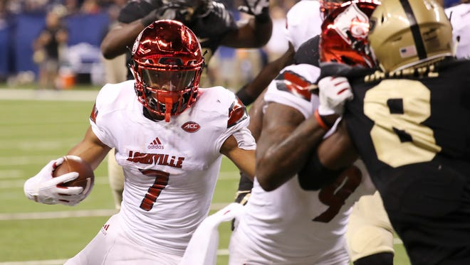 U of L's Reggie Bonnafon (7) gets some blocking on his way to scoring a touchdown against Purdue during their game at Lucas Oil Stadium in Indianapolis.Sep. 2, 2017