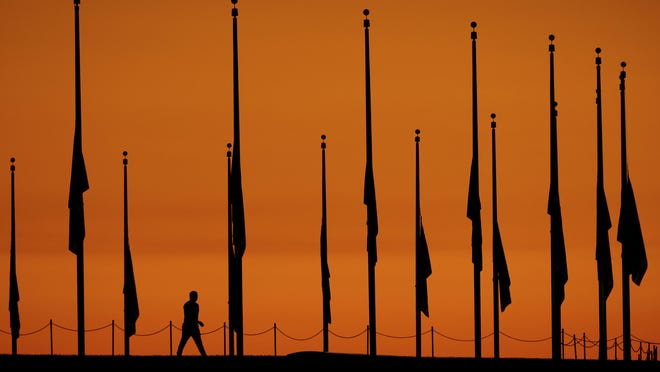 A visitor to the National Mall at daybreak in Washington, Tuesday, Oct. 3, 2017, walks past flags lowered to half-staff in honor of the victims killed in the Las Vegas shooting. (AP Photo/J. David Ake)