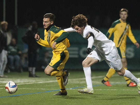 Vermont's Stefan Lamanna (11) and UMBC's Riley Collins (23) battles for the ball during the America East semifinal playoff game between the UMBC Retrievers and the Vermont Catamounts at Virtue Field on Wednesday night.