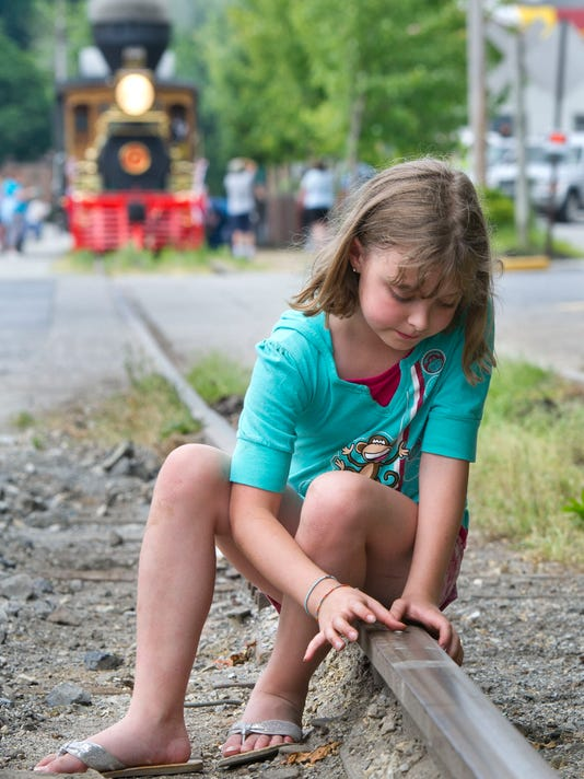 Bridget McMahon, age 9, of Glen Rock, checks out a penny she placed on the track that was squashed as the York No. 17 passed by for it's first public ride. McMahon wanted a keepsake to remember the day.  YORK DAILY RECORD/SUNDAY NEWS - PAUL KUEHNEL